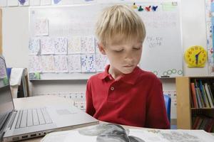 pojke läser bok i klassrummet foto