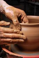 man gör keramik på det snurrande keramikhjulet foto