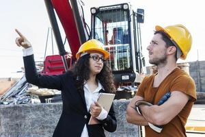 ung kvinnlig ingenjör talar om att arbeta med en arbetare foto