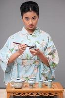 japansk kvinna som förbereder teceremoni foto