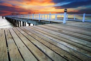 vacker gammal träbro på stranden med solnedgång himmel foto