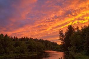 ljus dramatisk solnedgång över floden med skog längs floden foto