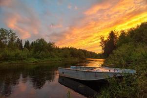 ljus dramatisk solnedgång över floden med båt i förgrunden foto