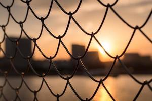 solnedgång genom staketet foto