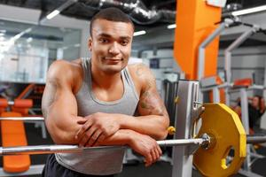 muskulös tyngdlyftare lutad på skivstång i gymmet foto
