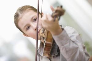 flicka som spelar fiol hemma foto