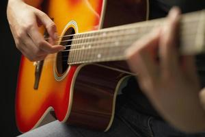 händer som spelar gitarr foto