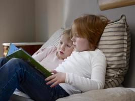 systrar som läser bok på sängen