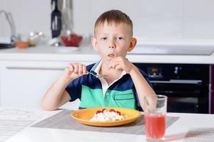 ung pojke äter tallrik med ost och frukt foto