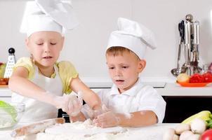glad liten pojke och flicka som lagar mat i köket