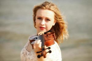 stående blond tjej med en fiol utomhus foto