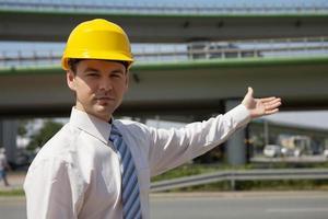 porträtt av arkitekt i hardhat som gör en gest på byggarbetsplatsen foto