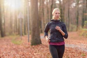 ganska passande ung kvinna som joggar i skogen foto