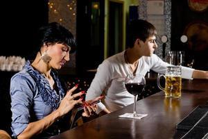 snygg kvinna i baren som skickar ett sms-meddelande foto