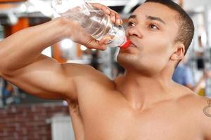 man dricksvatten i idrottshall foto