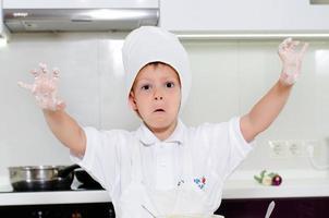 skrattande ung pojke med blomiga händer foto