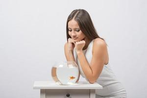 tjejen sitter nära akvariet med guldfisk och tittar på det foto