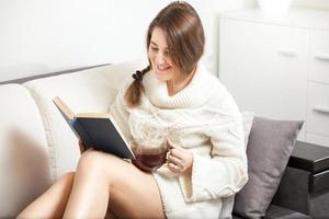 ung kvinna läser bok på soffan foto