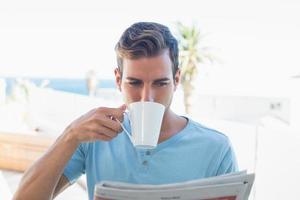 man dricker kaffe och läser tidningen foto