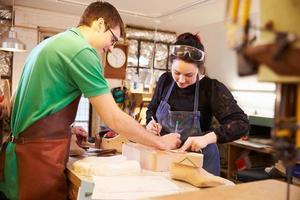 två unga skomakare som förbereder sko håller i en verkstad foto