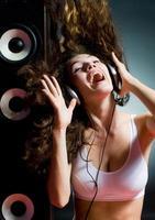 ung dam med hörlurar på att lyssna på musik foto