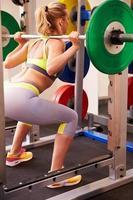 kvinna viktlyftande skivstång på en squat rack i ett gym foto