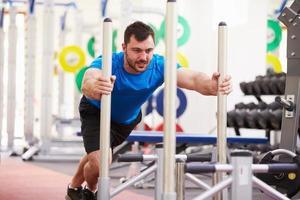 ung man tränar med hjälp av utrustning på ett gym foto