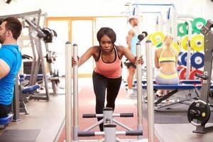 ung kvinna som tränar med hjälp av utrustning på ett gym foto