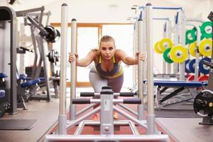 kvinna som tränar med hjälp av utrustning på ett gym foto