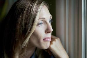 sorglig kvinna vid fönstret foto