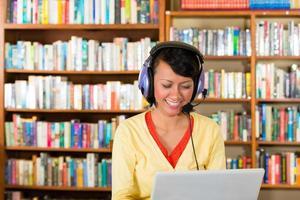 ung flicka i biblioteket med laptop och hörlurar foto