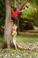 två barn som hjälper och klättrar på träd i parken foto