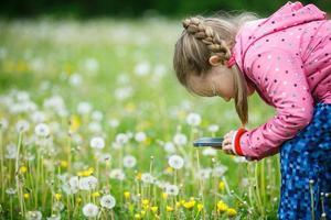 liten flicka som utforskar naturen med sin smarta telefon foto