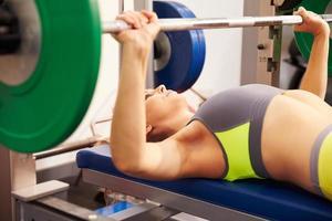 ung kvinna med skivstång bänk pressande vikter foto