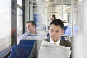 affärsman som läser tidningen på tåget