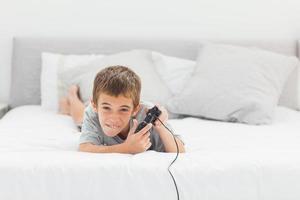 liten pojke som spelar videospel som ligger på sängen foto