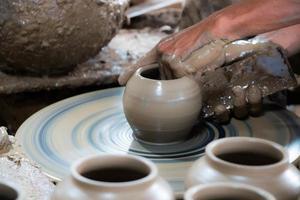 närbild av händer som arbetar lerkrukmakare foto