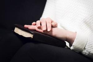 kvinna ber med bibeln foto