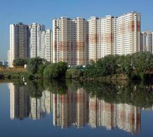 konstruerade byggnader över floden och klarblå himmel på sommaren foto
