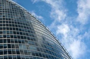 modern affärsglasbyggnad på bakgrund av en blå himmel