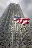 oss flagga vinkar mot byggnad och grå himmel foto