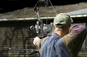 baksidan av en bågskytt som håller på att skjuta sin pil och båge foto