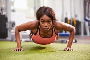 ung kvinna gör armhävningar på ett gym foto