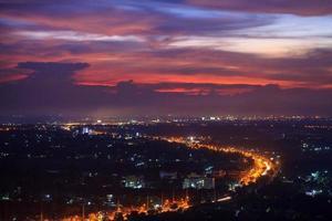 vägen till staden och solnedgången violett himmel. foto