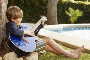 pojke spelar gitarr vid poolen foto