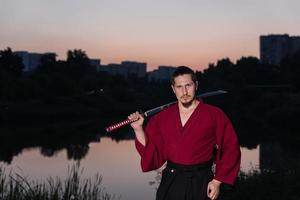 man i etnisk samurai japansk kläduniform med katana svärd foto