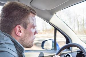 ung man som kör en bil foto