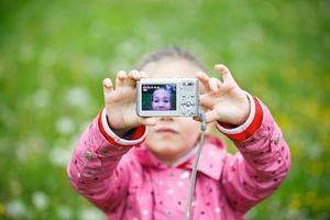 liten flicka som gör en selfie med digital kamera