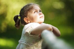 liten glad vacker flicka tittar upp foto