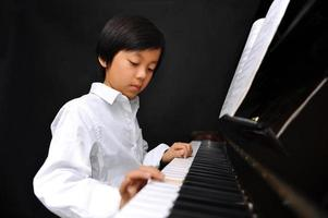 ung asiatisk pojke som spelar piano foto